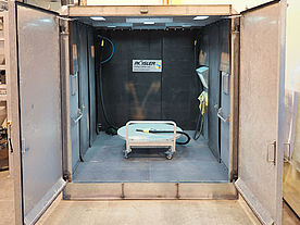 View into the interior of a modified free blasting chamber with loading cart and manual blasting station